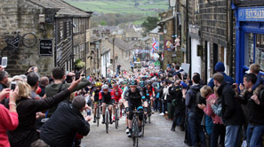 Cyclists riding up hill at Tour de Yorkshire as spectators cheer them on