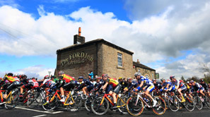 Group of cyclist at Tour De Yorkshire riding past a Bar and Resteraunt